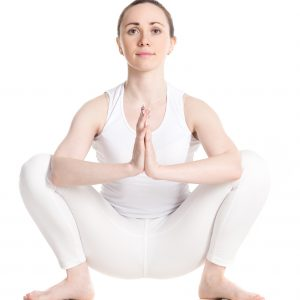 Sporty smiling beautiful young woman in white sportswear sitting in squat, Garland Pose, Malasana with hands in Namaste, studio full length shot on white background, front view, isolated